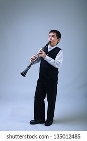 Happy boy playing on the clarinet enthusiastic