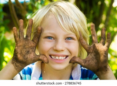 Happy boy playing outside with dirty hands