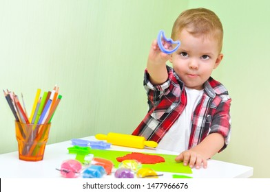 Happy boy playing with plasticine. A two-year-old baby boy in a red checked shirt sits at a table