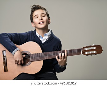 Happy boy playing with pleasure on acoustic guitar. Teenager boy with classic wooden guitar