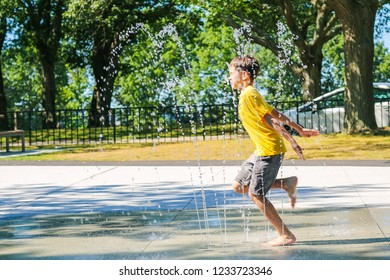 happy boy playing in a street fountain. the child enjoys playing in the fountain. Copy space for your text