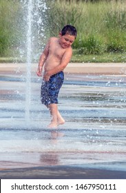 A happy boy plays in a fountain at a local splash pad in Michigan USA