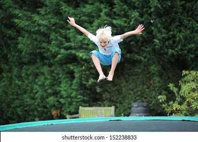 Happy boy plays outdoors in garden jumping high in the sky on trampoline