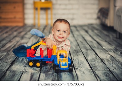 happy boy plays with toy car in the room