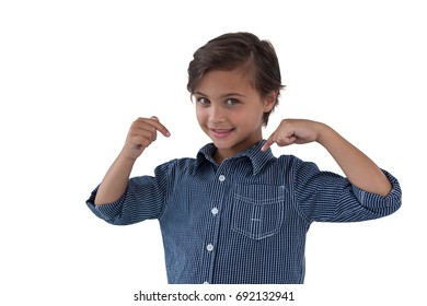Happy boy pointing at him against white background