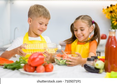 Happy boy pours sunflower oil in vegetable salad