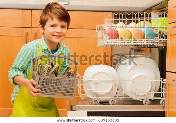 Happy boy pulling out cutlery of the dishwasher