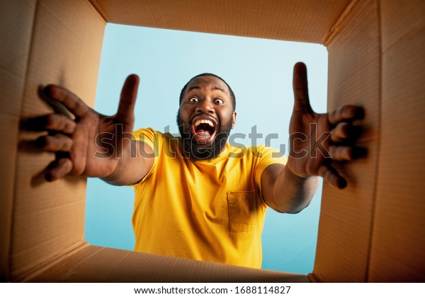 Happy boy receives a package from online shop order. happy and surprised expression. Blue background