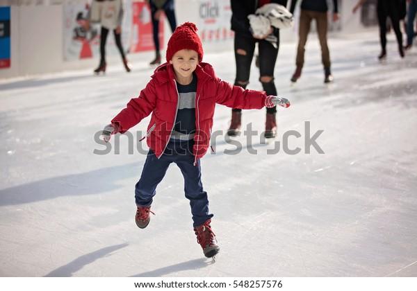 Happy Junge mit rotem Hut und Jacke, Schlittschuhlaufen am Tag, Spaß haben