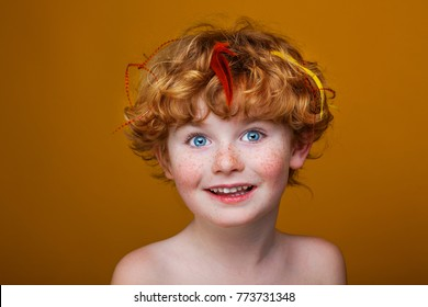 Happy boy, the red-haired boy with freckles and a cock's feather in the hair