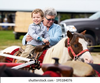 A happy boy rides a pony for the first time with his grandmother supporting him by his side.