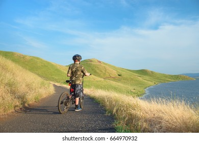 Happy boy riding his mountain bike on trail in hills