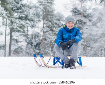 happy boy riding sled and having fun child play outdoors in snow sledding - Christmas Vacation Sled