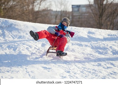 happy boy riding at the slide on snowy hill, outdoors
