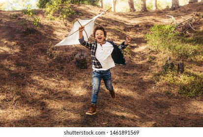 Happy boy running with a kite in hands over his head. Excited boy playing with a kite in forest.