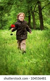 Happy boy running on grass, park