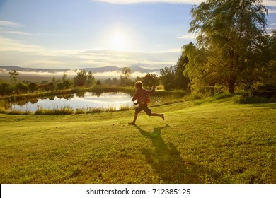 happy boy running through the meadow.  child having fun and playing outdoors in the early morning. Copy space for your text