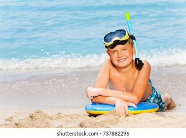 Happy boy with scuba mask and board for swimming