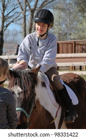 Happy boy seated on horseback participates in Hippo Therapy