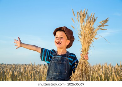 Happy boy with sheaf of wheat on the field