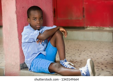 Happy boy sitting alone on the outside against a wall painted in red.Concept shy child, player, alone