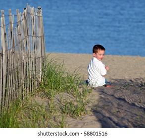 Happy boy sitting alone on a beach