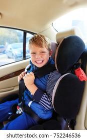 Happy boy sitting in child car seat in car. Preschool age boy in a booster seat