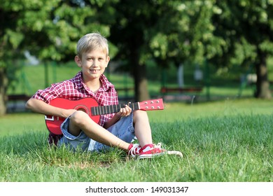 happy boy sitting on grass and play guitar