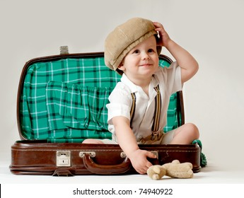 Happy boy sitting in a suitcase. He is wearing a hat. The suitcase is old.