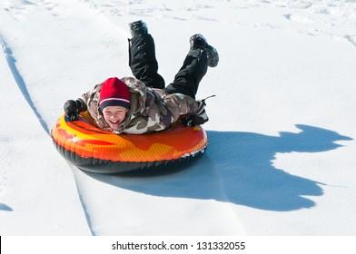 Happy boy sledding on a tube down a hill.
