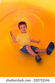 happy boy sliding in a plastic tube