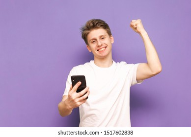 Happy boy with a smartphone in his hand, wearing a white T-shirt, looking into the camera and smiling, rejoices in victory with his arm raised, isolated on a purple background. Copyspace