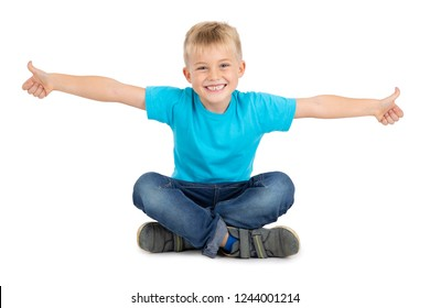 HAPPY BOY SMILING AND LIKING BY POINTING THUMB FINGERS UP WHILE SITTING WITH CROSS LEGS ISOLATED ON WHITE BACKGROUND