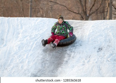 Happy boy with snow tube. Winter fun. Sliding down the hill on a snow tube
