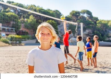 Happy boy standing on beach volleyball court