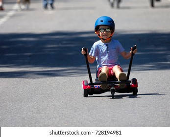 Happy boy standing on hoverboard or gyroscooter with kart accessory kit outdoor. New modern technologies