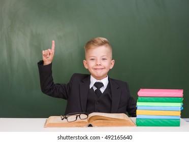 Happy boy in a suit points on empty green chalkboard