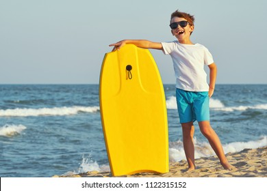 A happy boy in sunglasses in swimming trunks stands on the beach on golden sand and holds a swimming board, boogie board of yellow color against the blue sky and the sea with small waves in sunny sun