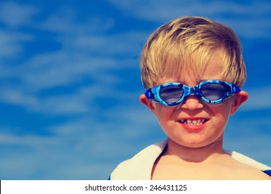 happy boy in swimming goggles on summer sea vacation