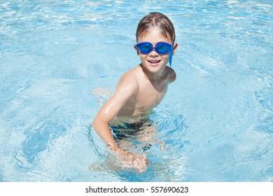 Happy boy in a swimming pool. Cute little kid boy having fun in a swimming pool. Outdoors. Sport activities for children.