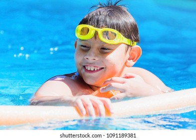 Happy boy at the swimming pool with swimming goggles on head , floating with swim noodles on a summer day.