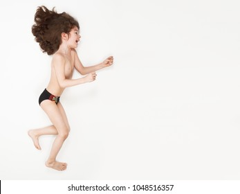 eb080484cc Happy boy in swimming trunks roving against a strong wind over light  background