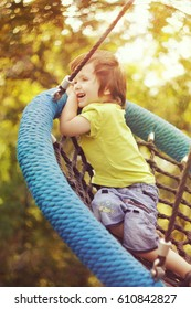 Happy boy swinging on a swing in the Park on a Sunny summer day