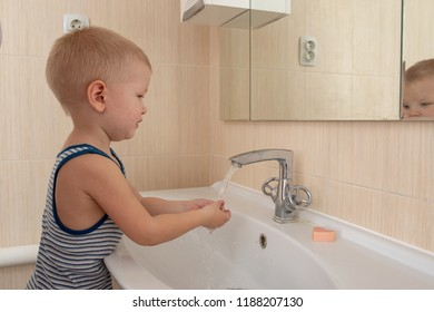 Happy boy taking bath in kitchen sink. Child playing with Toothbrush in sunny bathroom with window. Little baby bathing. Water fun for kids. Hygiene and skin care for children. Bath room interior