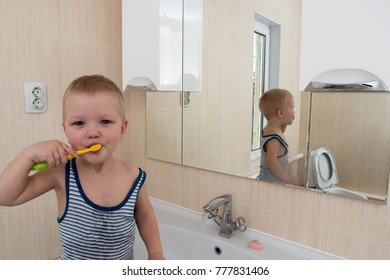 Happy boy taking bath in kitchen sink. Child playing with foam and soap bubbles in sunny bathroom with window. Baby bathing. Water fun for kids. Hygiene and skin care for children. Bath room interior