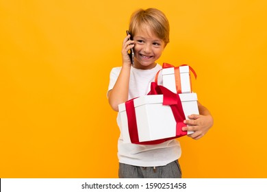 happy boy talking on the phone and holding a gift box on a yellow background