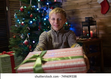 Happy boy teenager gives a gift for Christmas! A child with a gift for Christmas in the room holds out a gift