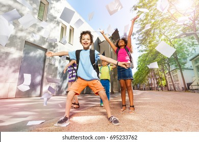 Happy boy throws papers in the air very excited