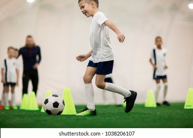 Happy boy in uniform kicking the ball while running around cones during training