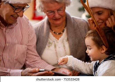 happy boy using tablet, family spending Christmas time together